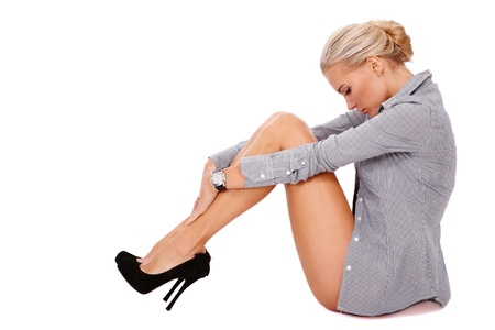 stilettos: Young beautiful slim sexy blond woman in striped shirt and stilettos sitting on white background