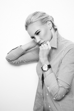 esitazione: Scatto in bianco e nero di giovane bella donna sexy bionda sottile pensierosa ascoltando il suo orologio biologico ticchettare