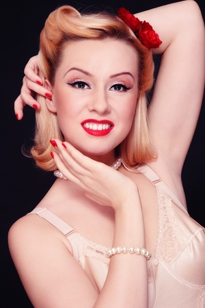50s fashion: Beautiful young sexy smiling woman with vintage make-up and hairstyle