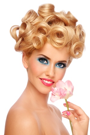 Portrait of young beautiful smiling happy blond woman with fancy make-up and flower in hand on white background