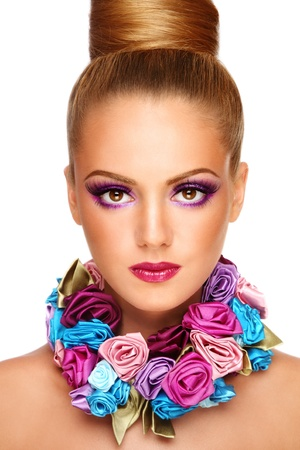Portrait of young beautiful tanned girl with stylish violet make-up and fancy necklace, on white background