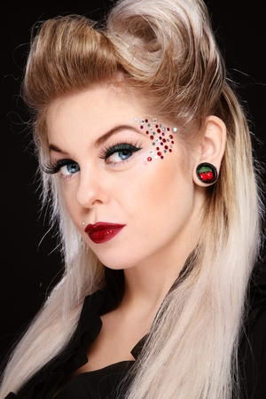 Portrait of young beautiful girl with fancy make-up and hairdo photo