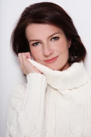 mujeres maduras: Retrato de atractivo peinado sano feliz y sonriente mujer de mediana edad en blanco jersey Foto de archivo