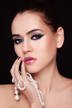 Portrait of young beautiful woman with stylish make-up and pearl  in hand photo
