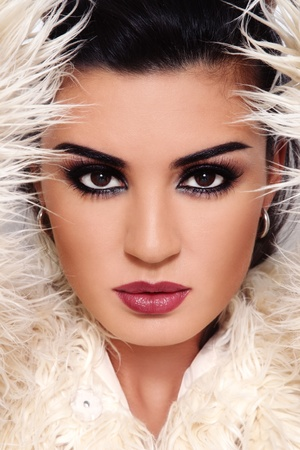 Close-up portrait of young beautiful brunette with stylish make-up with white fur around