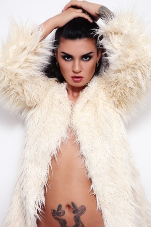 Young beautiful sexy woman with stylish make-up in fur coat, over white wall photo