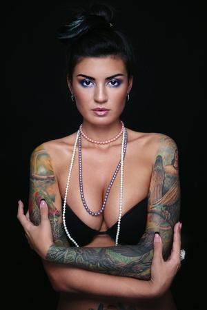 tieten: Jonge mooie sexy brunette met prachtige tatoeage op haar armen Stockfoto