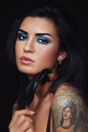 Portrait of young beautiful brunette with stylish turquoise make-up and feather in hand photo