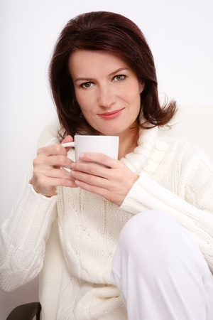 woman sweater: Attractive smiling middle-aged woman in knitted pullover sitting on the armchair with cup in hands, over white wall