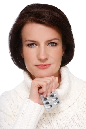 Portrait of attractive healthy middle-aged woman in knitted pullover with pack of pills in hand, over white background photo