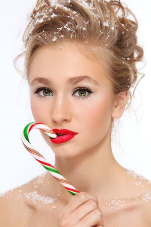 guilty pleasure: Portrait of young beautiful girl with stylish make-up and hairdo, candy cane and snowflakes in her hair