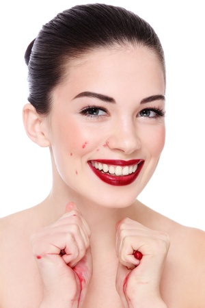 Portrait of young beautiful happy laughing woman squeezing pomegranates in her hands, over white background photo
