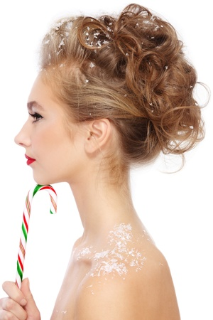 Profile of young beautiful girl with fancy stylish hairdo and candy cane in hand, over white background Stock Photo