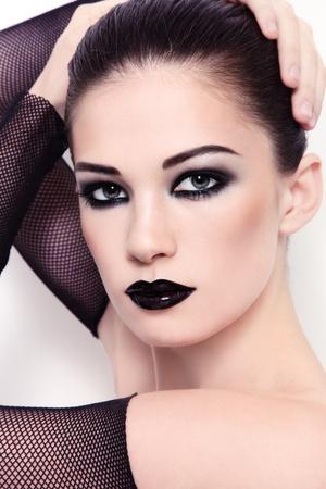 Portrait of young beautiful woman wiith stylish black make-up