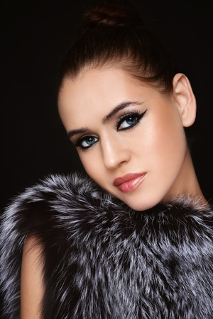 Portrait of young beautiful model with trendy make-up  in fur outfit