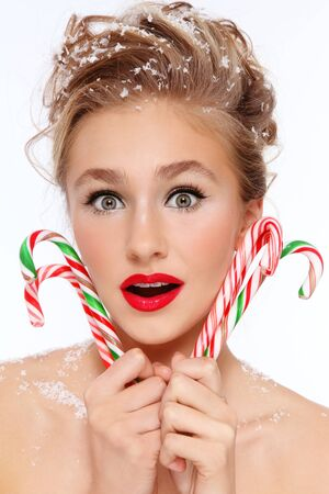 guilty pleasure: Retrato de joven bella joven sorprendido con los bastones de caramelo en las manos y los copos de nieve en el pelo Foto de archivo