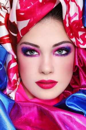 Portrait of young beautiful woman with fancy sparkly make-up and bright fabrics around her face photo