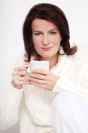 Attractive smiling middle-aged woman in knitted pullover sitting on the armchair with cup in hands, over white wall Stock Photo - 11754944