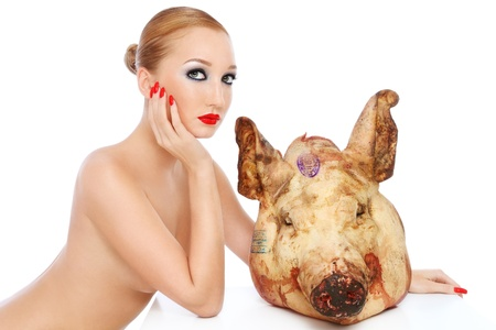 cut off head: Conceptual image of young beautiful sexy woman with dead pigs head, over white background