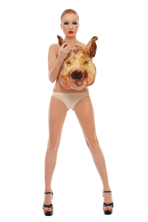 Conceptual image of young beautiful slim sexy woman in stilettos with dead pig's head, over white background photo
