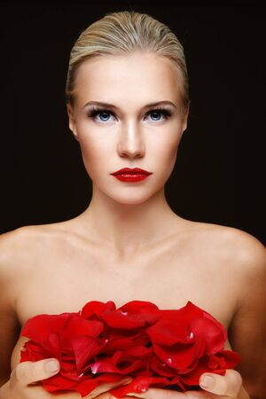 red breast: Young beautiful sexy blond woman with red rose petals in hands Stock Photo