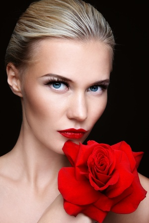 Close-up portrait of young beautiful sexy blond woman with red rose
