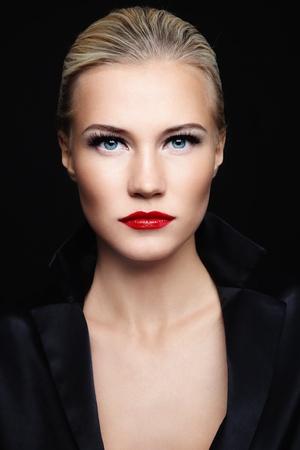 sexualidad: Joven y bella mujer rubia glamorosa en la chaqueta de seda negro sobre fondo oscuro