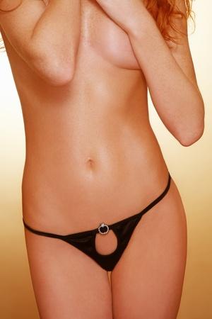 Torso of slim sexy tanned hot redhead girl in hot black panties photo
