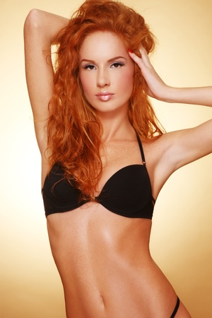 Beautiful slim tanned sexy redhead girl in black bra photo