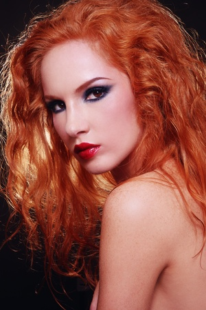 Portrait of young beautiful sexy woman with fiery red curly hair and stylish make-up photo