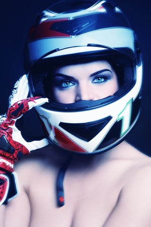 Beautiful sexy woman with stylish makeup in biker helmet and gloves photo