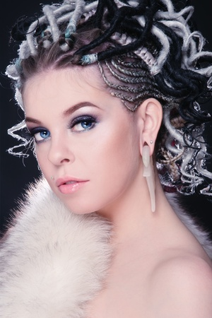 Beautiful young sexy girl with fancy hairstyle of dreads and white fur on her body photo