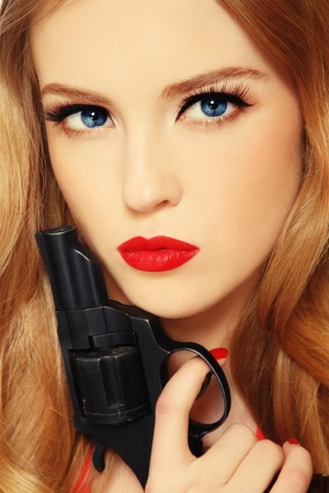 Close-up portrait of beautiful young blond woman with revolver in hand photo