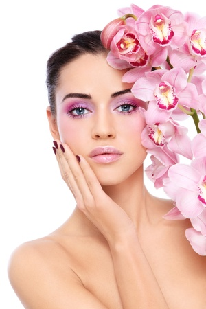 Young beautiful tanned woman with fresh make-up and gorgeous pink orchid, over white background photo
