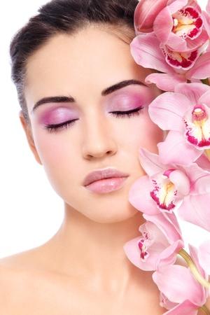 Joven hermosa mujer morena, con demasiado maquillaje y orquídea rosa, sobre fondo blanco Foto de archivo - 12325236