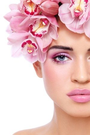 Close-up shot of young beautiful tanned sexy woman with fresh make-up and orchids in her hair, on white background Stock Photo - 12325216