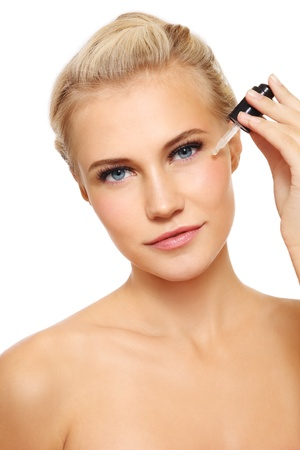serum: Portrait of young fresh beautiful healthy woman applying serum on her face, over white background