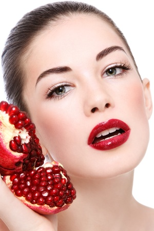 Portrait of young beautiful woman with pomegranates in her hands, on white background Stock Photo - 12325232
