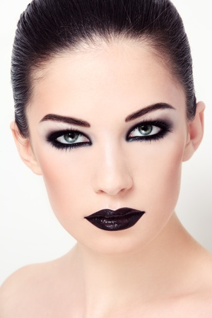 Close-up portrait of young beautiful woman with stylish black make-up photo