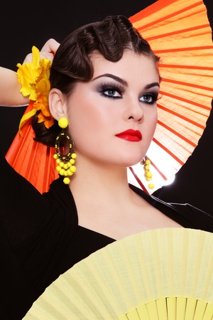 Beautiful stylish girl in flamenco costume with two colorful fans photo