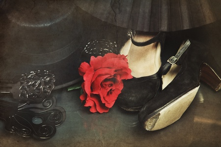 Still-life with bright flamenco accessories on vintage grainy damaged background. Shoes, hair flower, fan, combs and hat Stock Photo
