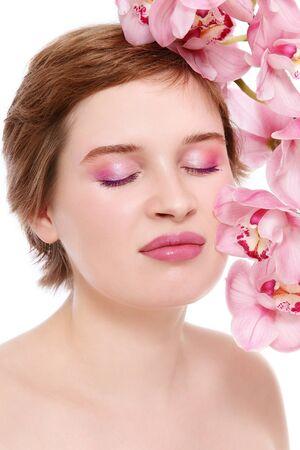 Mujer hermosa joven con demasiado maquillaje y orquídea rosa, sobre fondo blanco Foto de archivo - 12658988