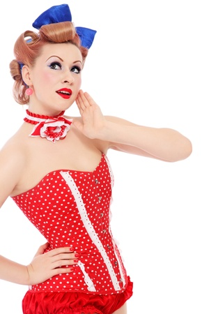 Beautiful young sexy pin-up promo girl in polka dot corset looking upwards with curious expression, on white background Stock Photo - 12658991