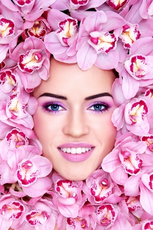 Portrait of young beautiful smiling woman with stylish make-up and pink orchids around her face Stock Photo