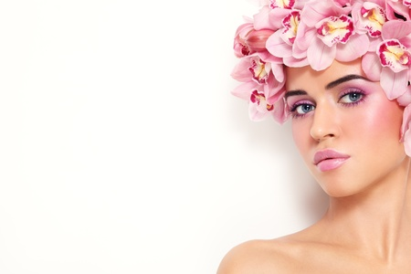 Young beautiful tanned sexy woman with fresh make-up and orchids in her hair over white wall Stock Photo - 13425911