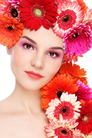 Young beautiful woman with fresh make-up and colorful gerberas in her hair, on white background Stock Photo - 13425969