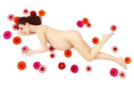 Young beautiful pregnant woman lying on white background with colorful gerberas around Stock Photo - 13425928