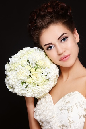 Portrait of beautiful bride with stylish make-up and hairdo holding bouquet in her hand