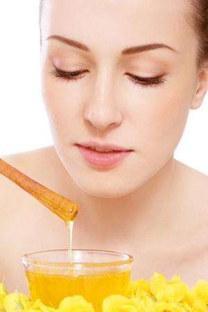 exfoliation: Young beautiful healthy woman making honey facial mask Stock Photo