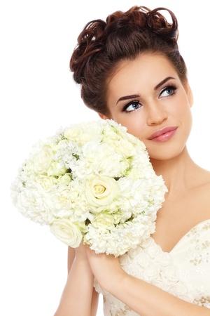 Portret van jonge mooie bruid met stijlvolle make-up en kapsel zoek naar boven, over witte achtergrond